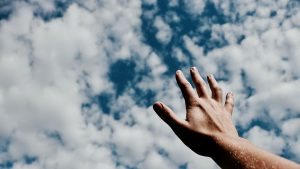 Hand reaching toward the clouds